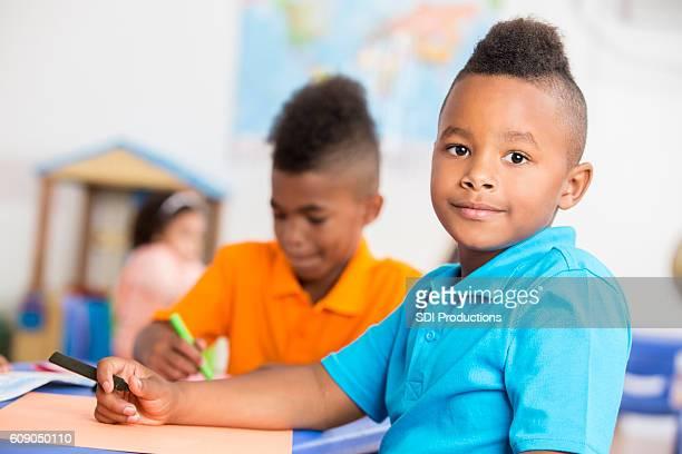 Handsome African American boy has fun in class