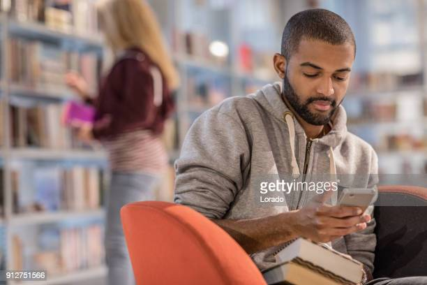 handsome afro american university student studying alone in a campus library - linguistics stock pictures, royalty-free photos & images