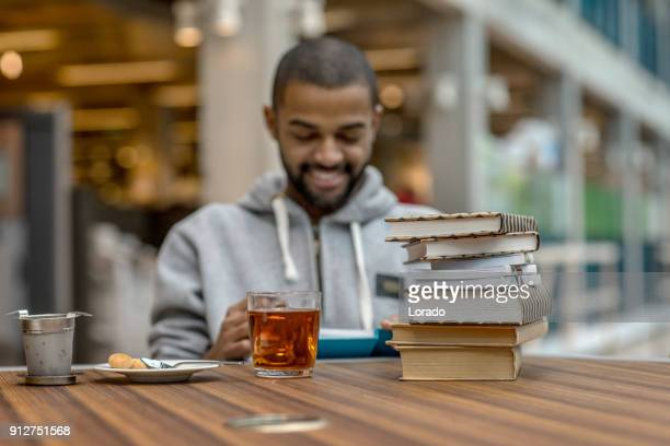 handsome afro american university student studying alone in a study hall - linguistics stock pictures, royalty-free photos & images