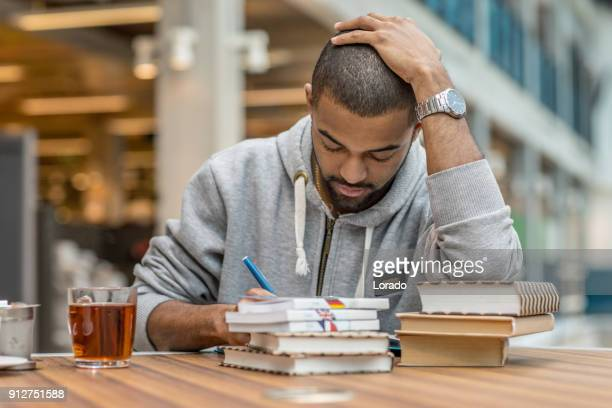 Handsome afro american university student studying alone in a study hall