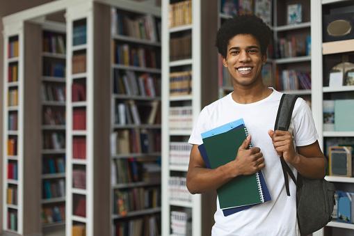 Handsome afro student posing on bookshelves background 1171062918