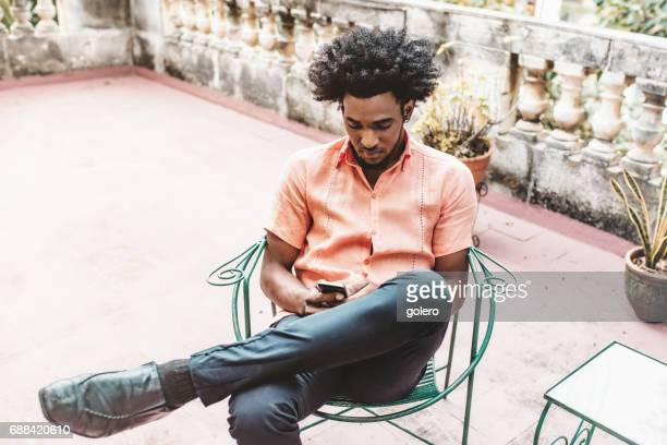 handsome afro-caribbean cuban man in chair looking on mobile