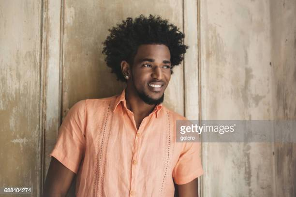 handsome afro-caribbean cuban man leaning on wooden wall
