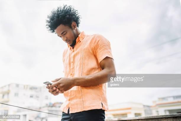 hübscher Afro-karibischen kubanischen Mann im Freien auf der Suche auf dem Handy