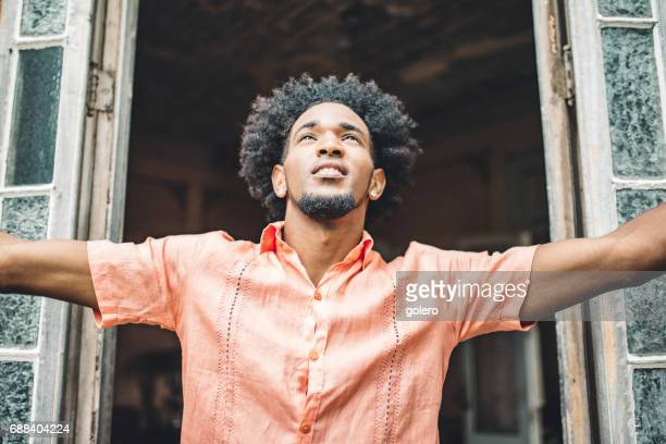 handsome afro-caribbean cuban spreading arms in front of window
