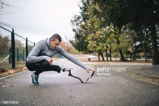handsome amputee athlete flexing his muscles - fake man stock photos and pictures
