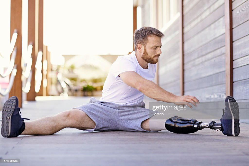 Handsome amputee male working out at summer beach location : Stock Photo