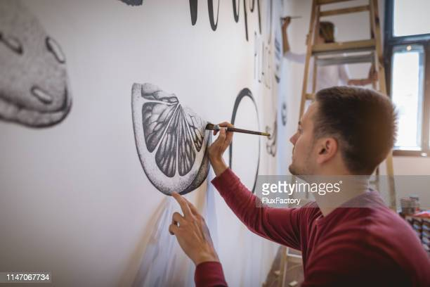 handsome artist painting on the wall - artist stock pictures, royalty-free photos & images