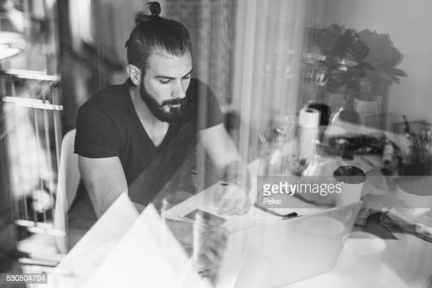 Handsome artist using laptop in his atelier