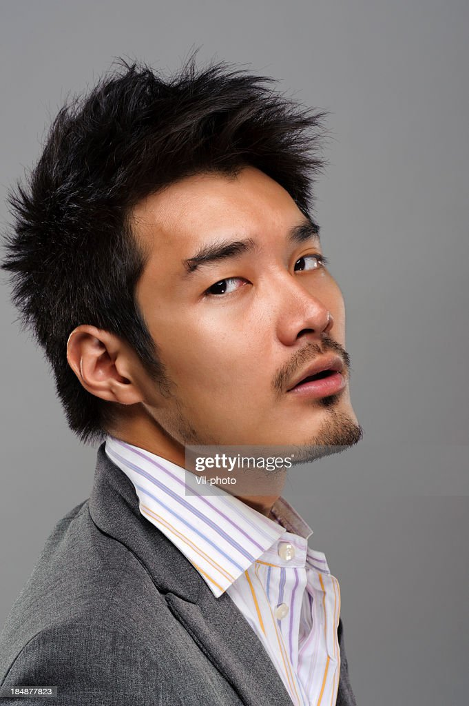 A handsome Asian man in a dress shirt and tuxedo : Stock Photo