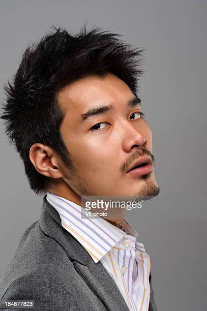 A handsome Asian man in a dress shirt and tuxedo