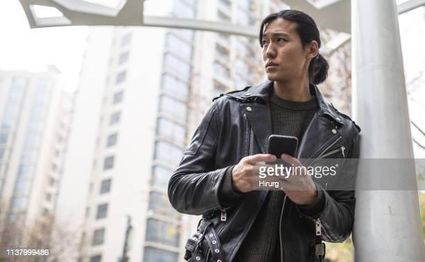 ハンサムなアジア人はスマートフォンを使用しています - レザージャケット ストックフォトと画像