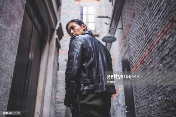 homem bonito asiático, olhando por cima do ombro - jaqueta - fotografias e filmes do acervo