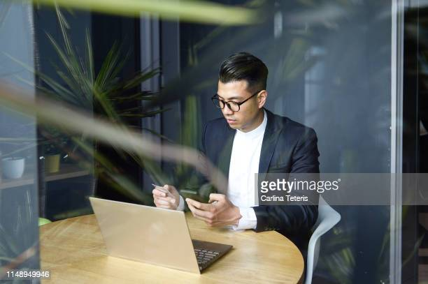 handsome asian man making online purchases with a credit card - image stock pictures, royalty-free photos & images