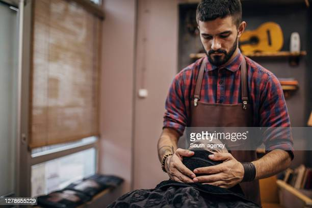 handsome barber covering face of male client with hot towel before shaving - shaved stock pictures, royalty-free photos & images