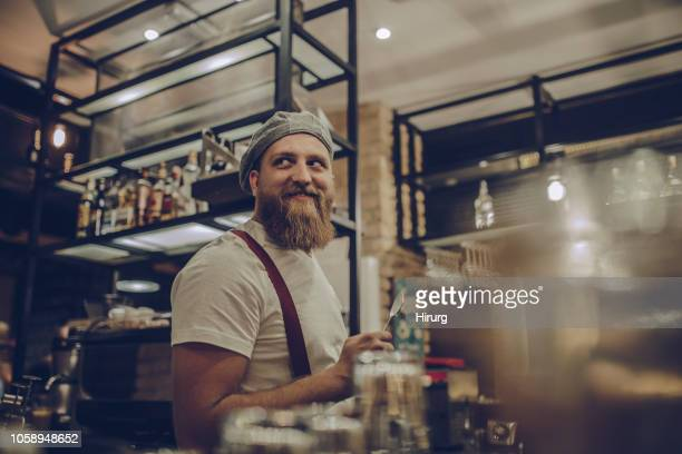 handsome bearded bartender working - charming stock pictures, royalty-free photos & images