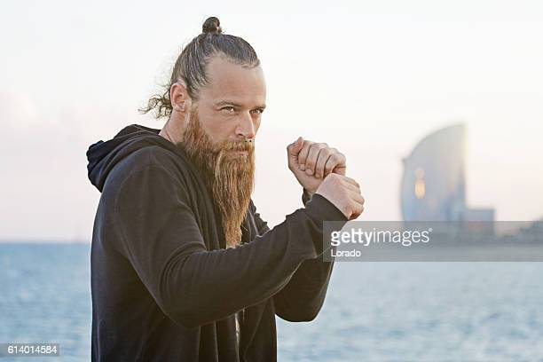 Handsome bearded boxer shadow boxing by the sea