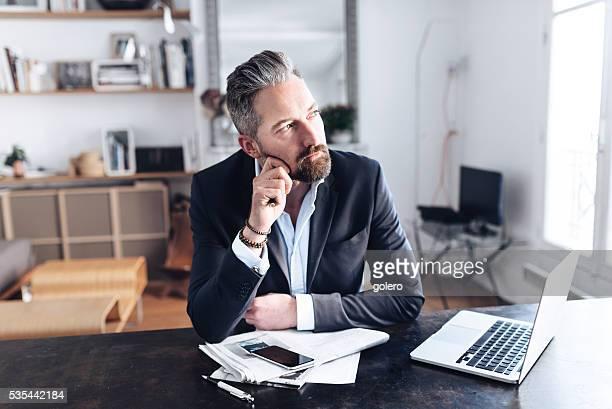 Beau barbu homme d'affaires penser au bureau de travail