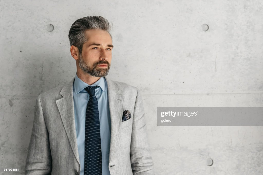 handsome bearded businessman standing in front of concrete wall : Stock Photo