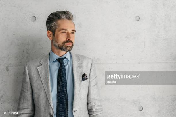 handsome bearded businessman standing in front of concrete wall - male model stock photos and pictures