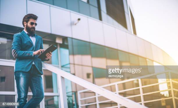 Handsome bearded businessman using digital tablet in front of the office