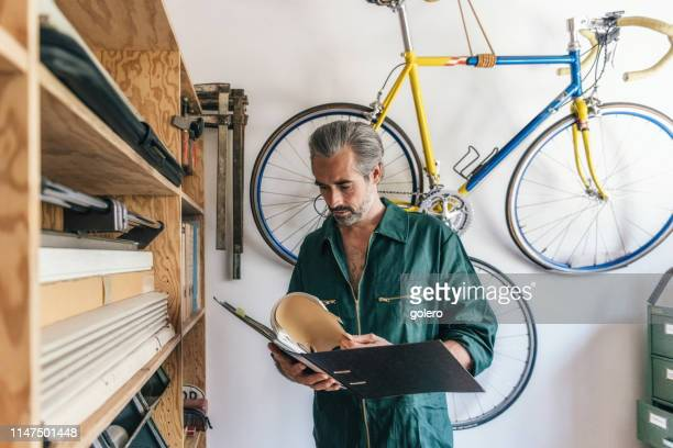 handsome bearded craftsmen reading in folder - bureaucracy stock pictures, royalty-free photos & images
