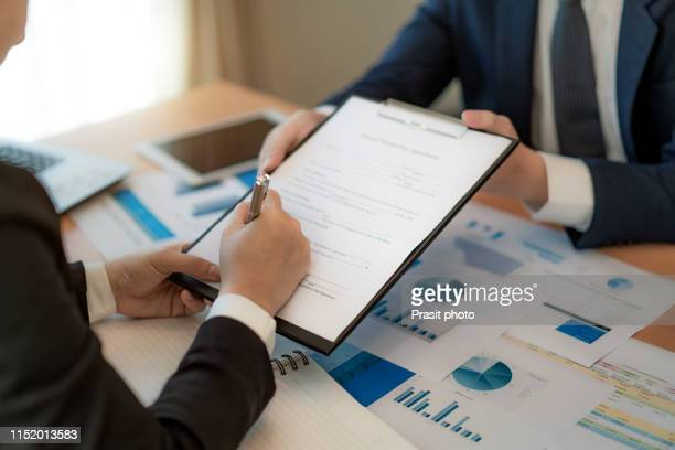 handsome bearded entrepreneur as his business partner finally signing important contract in office. - abmachung stock-fotos und bilder
