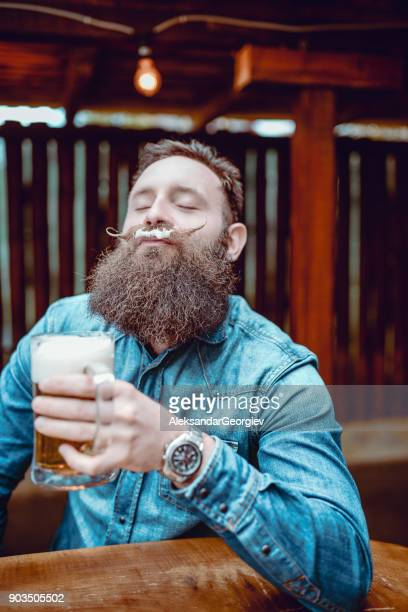 handsome bearded hipster person drinking beer in pub and enjoying - barba peluria del viso foto e immagini stock