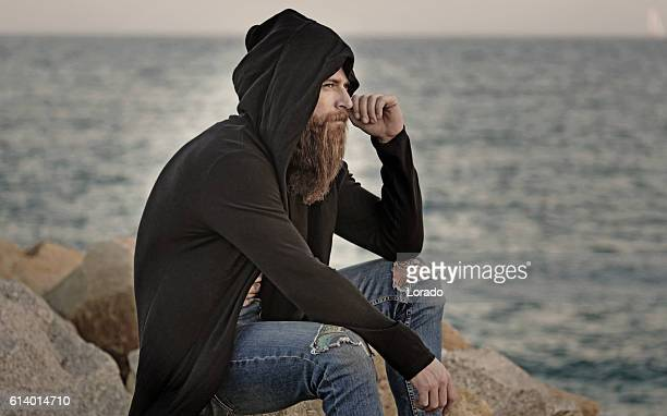 Handsome bearded hooded man sitting alone by the sea