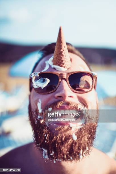 handsome bearded male playing with ice cream - beach fun stock pictures, royalty-free photos & images