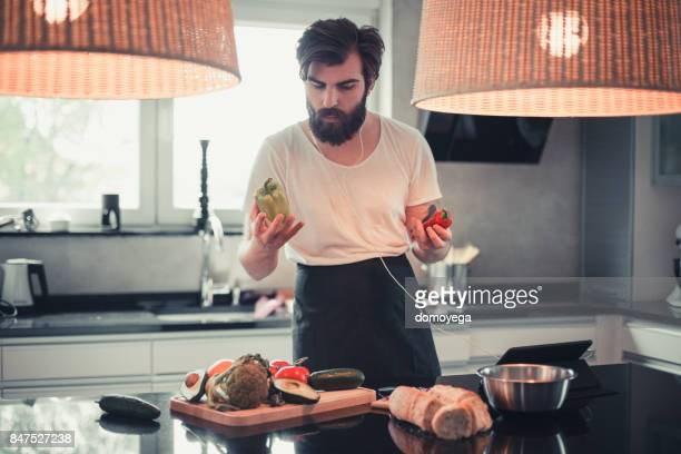 Handsome bearded man cooking and listening to music in the kitchen