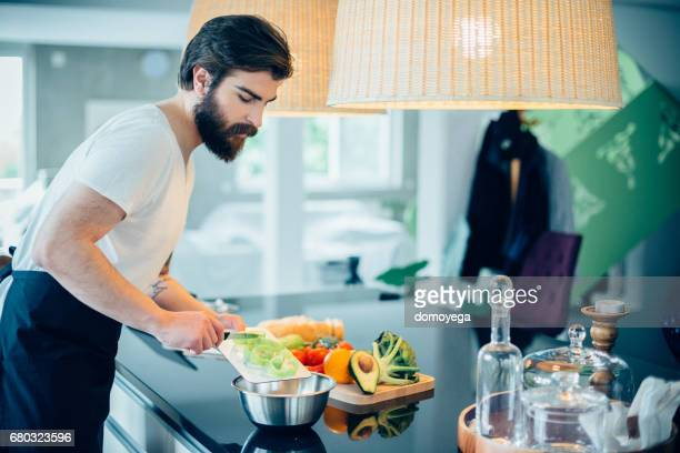 Handsome bearded man cutting vegetables to prepare healthy meal