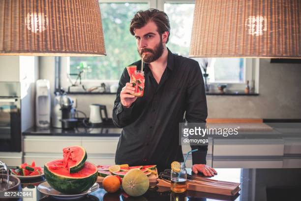 Handsome bearded man drinking watermelon juice and making fruit salad in the kitchen