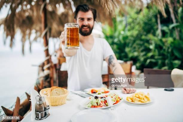 Handsome bärtiger Mann Essen im Restaurant am Meer in Griechenland