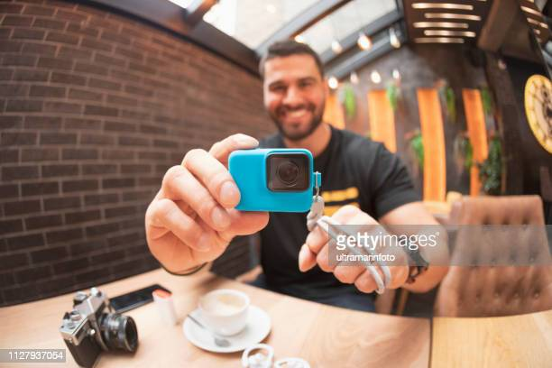 handsome bearded man filming with action camera, using a gopro  on coffee break in a  cafe restaurant  freelance work - body camera stock pictures, royalty-free photos & images