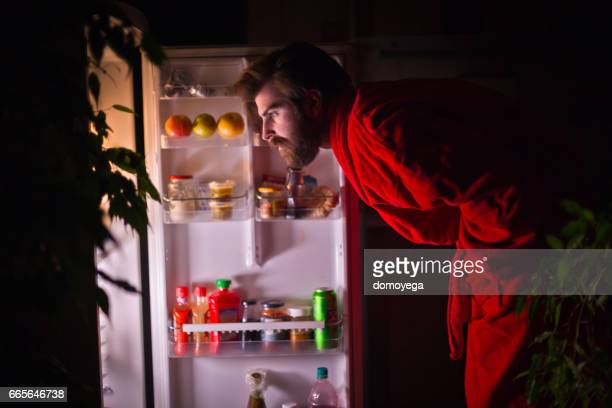 Handsome bearded man in front of the refrigerator during the night