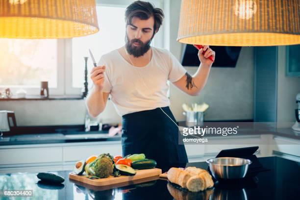Hübscher bärtigen Mann Musik hören, Spaß haben und gesunde Mahlzeit kochen