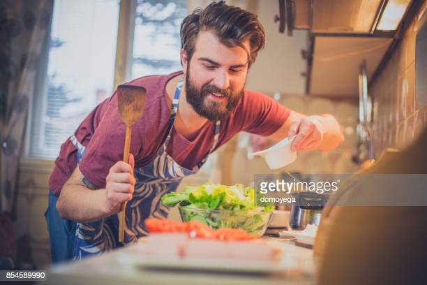 Handsome bearded man making healthy meal in the kitchen
