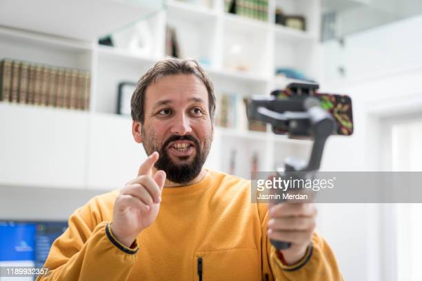 handsome bearded man making video with smartphone indoors - video still stock pictures, royalty-free photos & images