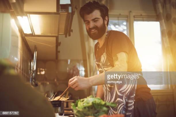 Bel homme barbu, préparation des repas dans la cuisine