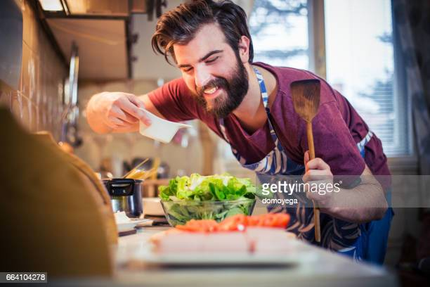 Handsome bearded man preparing healthy meal in the kitchen