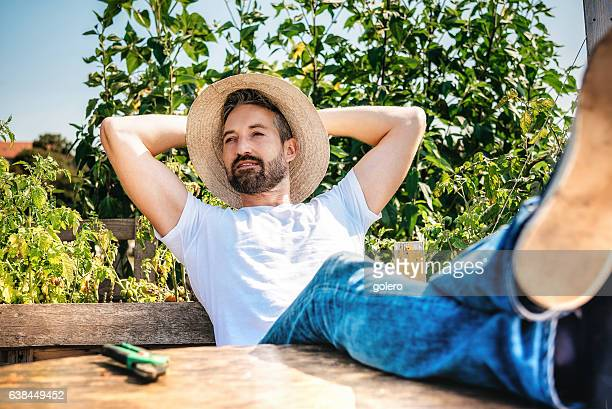 handsome bearded man relaxing with feet on table in garden