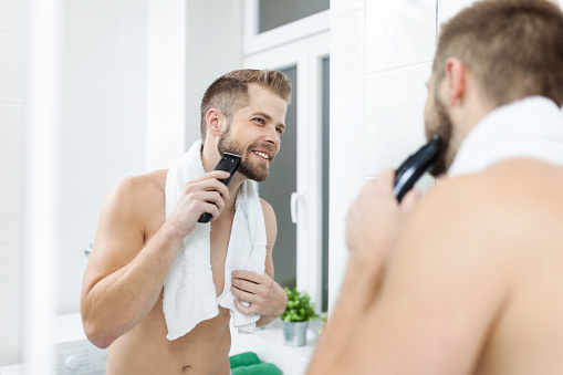 Handsome bearded man trimming his beard with a trimmer 913432444