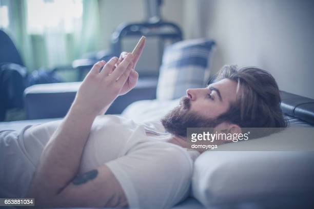 Handsome bearded man using phone in the bed