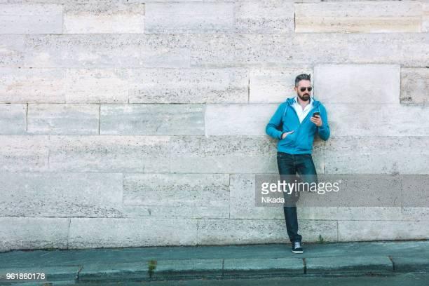 bel homme barbu à l'aide de téléphone - adulte d'âge mûr photos et images de collection