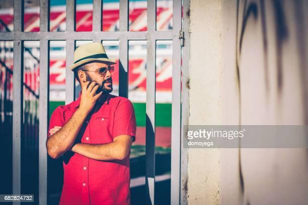 handsome bärtiger mann mit hut vor dem stadion-tor - liberty stadion stock-fotos und bilder