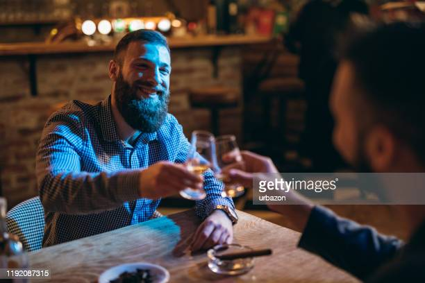 handsome bearded men drinking whiskey - bourbon whiskey stock pictures, royalty-free photos & images