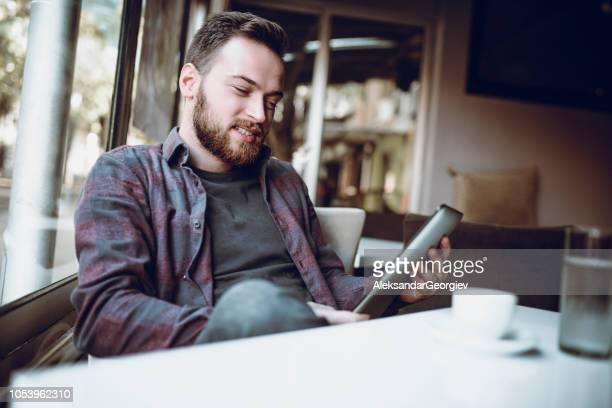 Handsome Bearded Men Enjoying His New Digital Tablet In Coffee Bar
