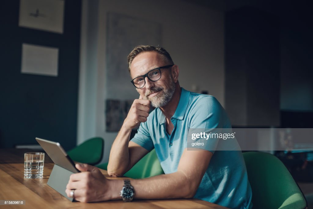 handsome bearded midaged man at table with digital tablet : Stock Photo