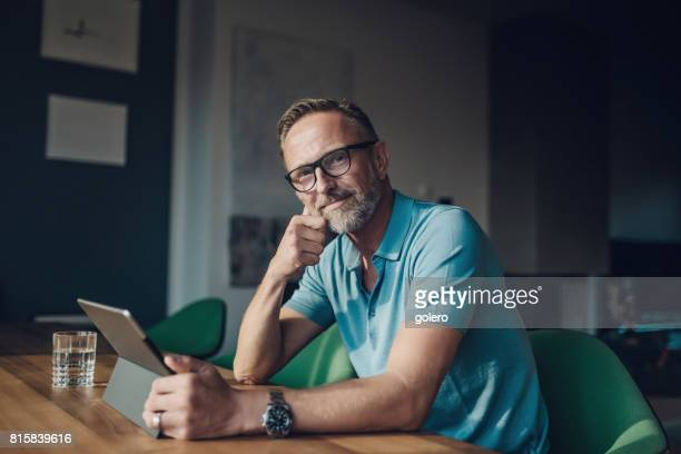 handsome bearded midaged man at table with digital tablet - common stock pictures, royalty-free photos & images